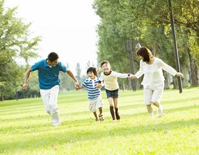 原っぱで走る家族